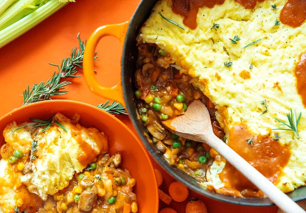 A pot filled with freshly cooked vegetarian shepard's pie next to an orange bowl filled with a serving