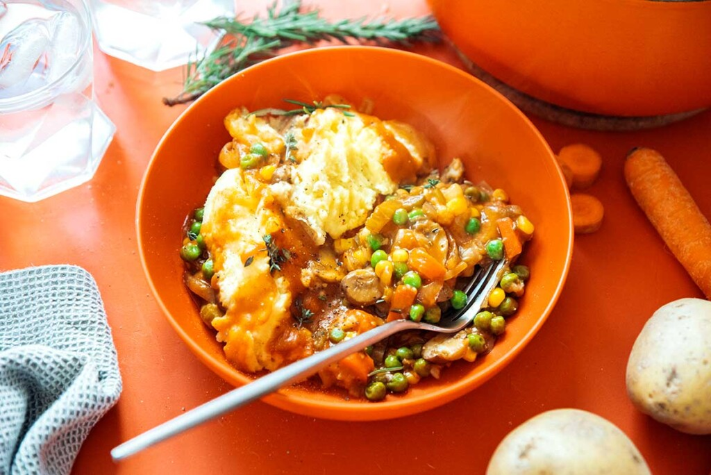 An orange bowl filled with a serving of vegetarian shepard's pie