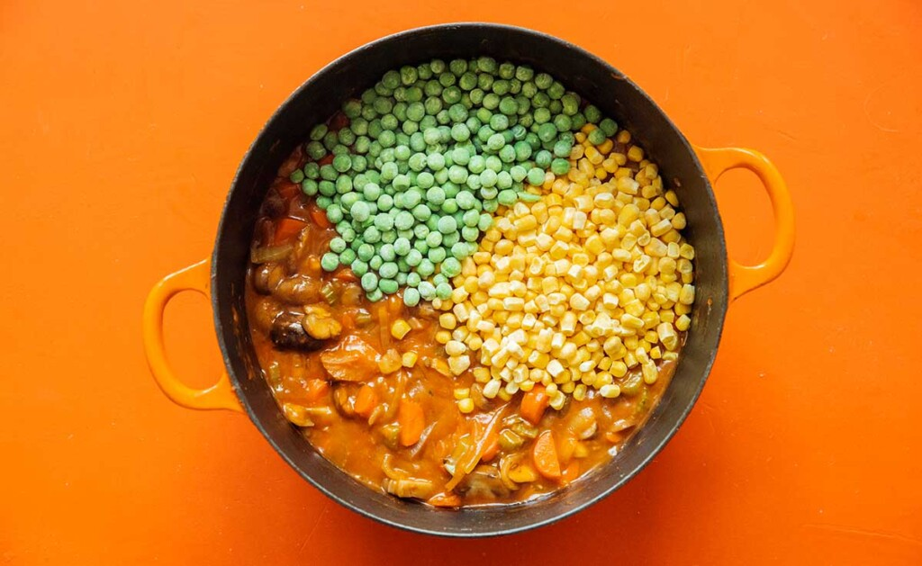 A large pot filled with veggie shepard's pie ingredients with frozen peas and canned corn poured on top