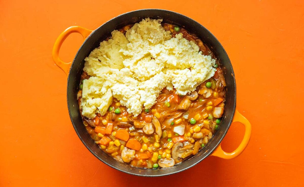 A large pot filled with veggie shepard's pie ingredients with mashed potatoes on top