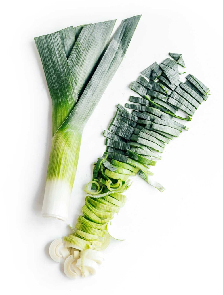 Two leek halves side by side, one whole and one chopped, detailing how to cut leeks