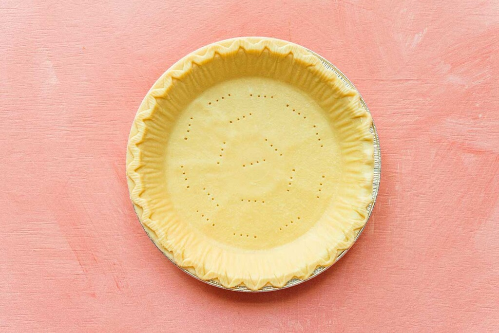An uncooked, empty pie crust in a tin cooking tray on a light pink background
