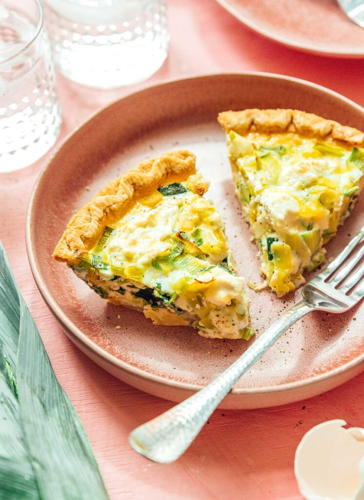 A plate filled with two thick pieces of goat cheese and leek quiche