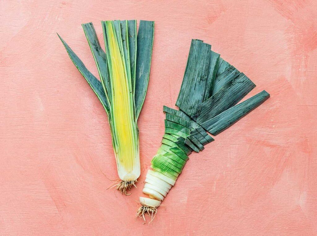 One leek cut in half lengthwise, with one half facing up and the other sliced into small pieces