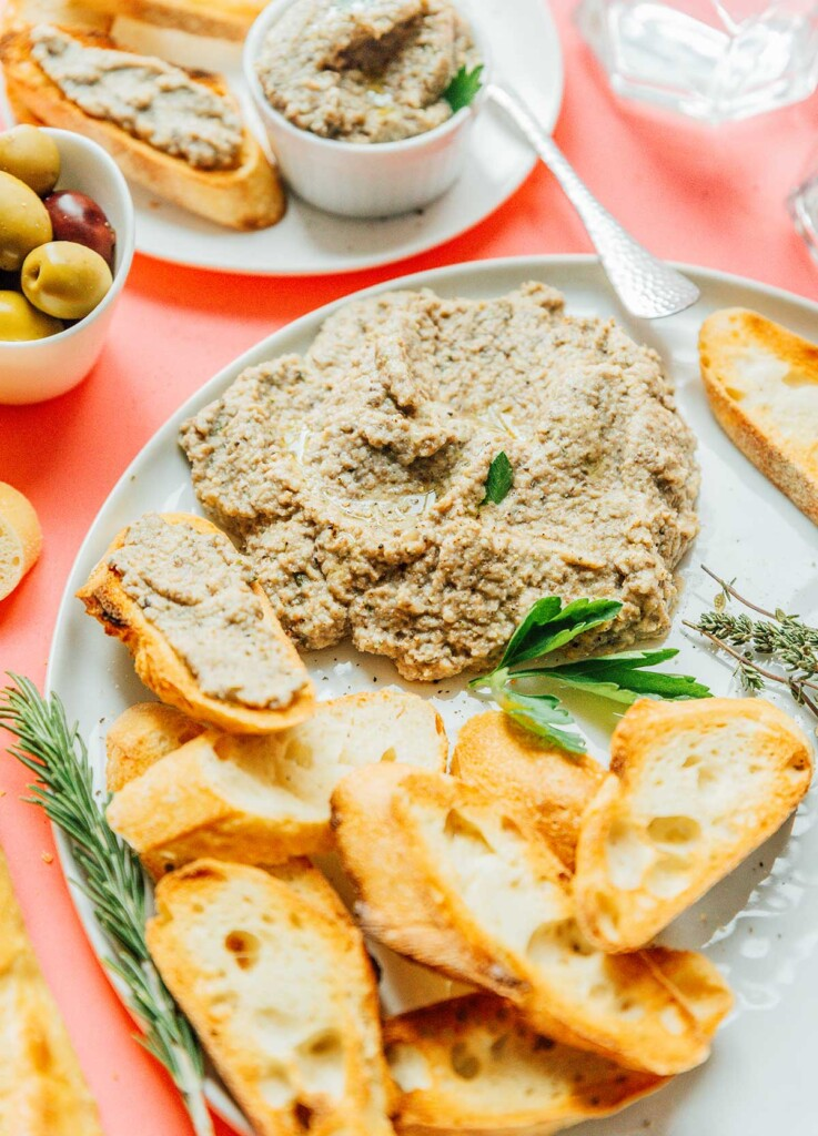 A large dollop of mushroom pâté on a white plate with slices of French bread