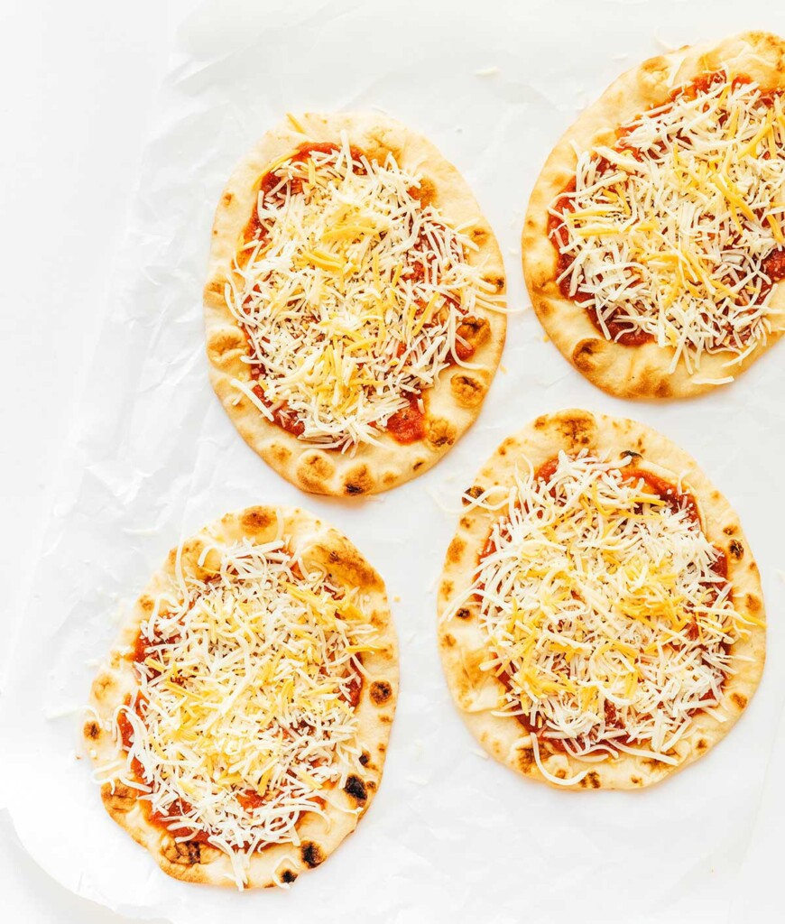 Four uncooked naan pizzas topped with sauce, mozzarella, and cheddar cheese