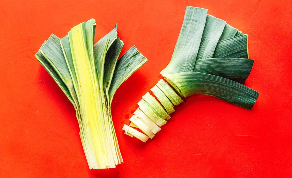 Two leek halves cut down the center and laid on a red background, the left half whole and the right half sliced into half moons