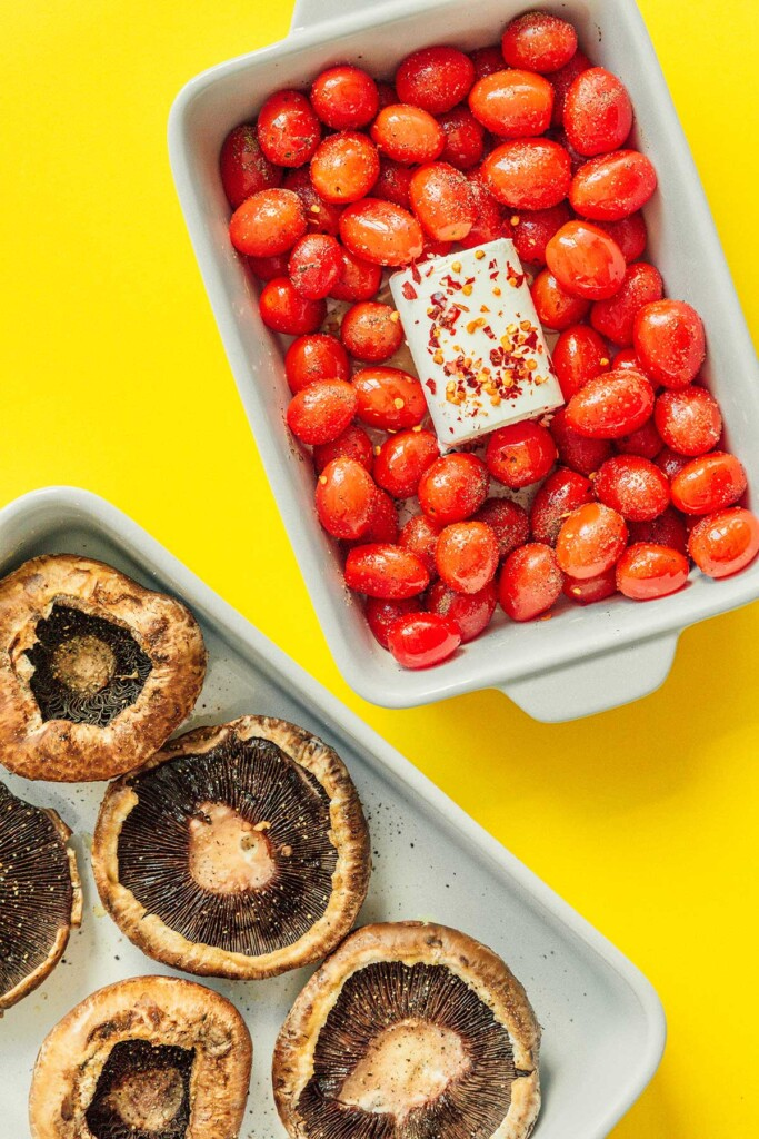 A casserole dish filled with uncooked cherry tomatoes and goat cheese beside a baking tray filled with portobello mushrooms