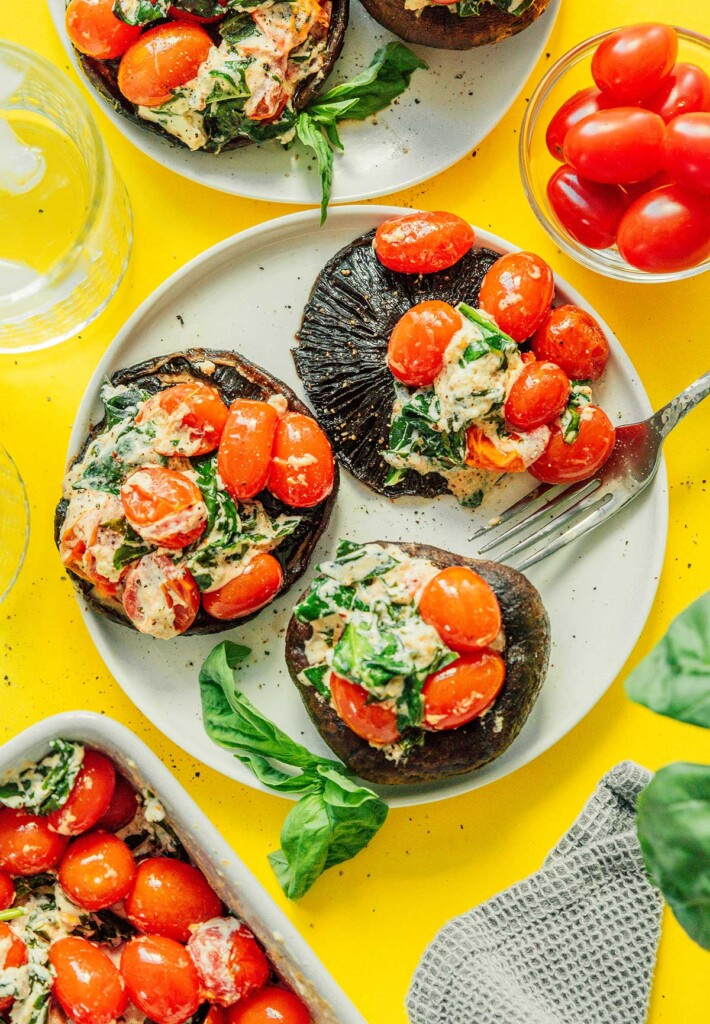 Three roasted tomato and goat cheese stuffed mushrooms on a white plate