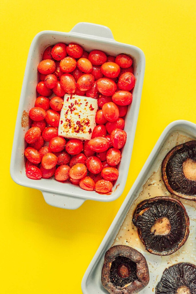 A casserole dish filled with baked cherry tomatoes and goat cheese beside a baking tray filled with baked portobello mushrooms