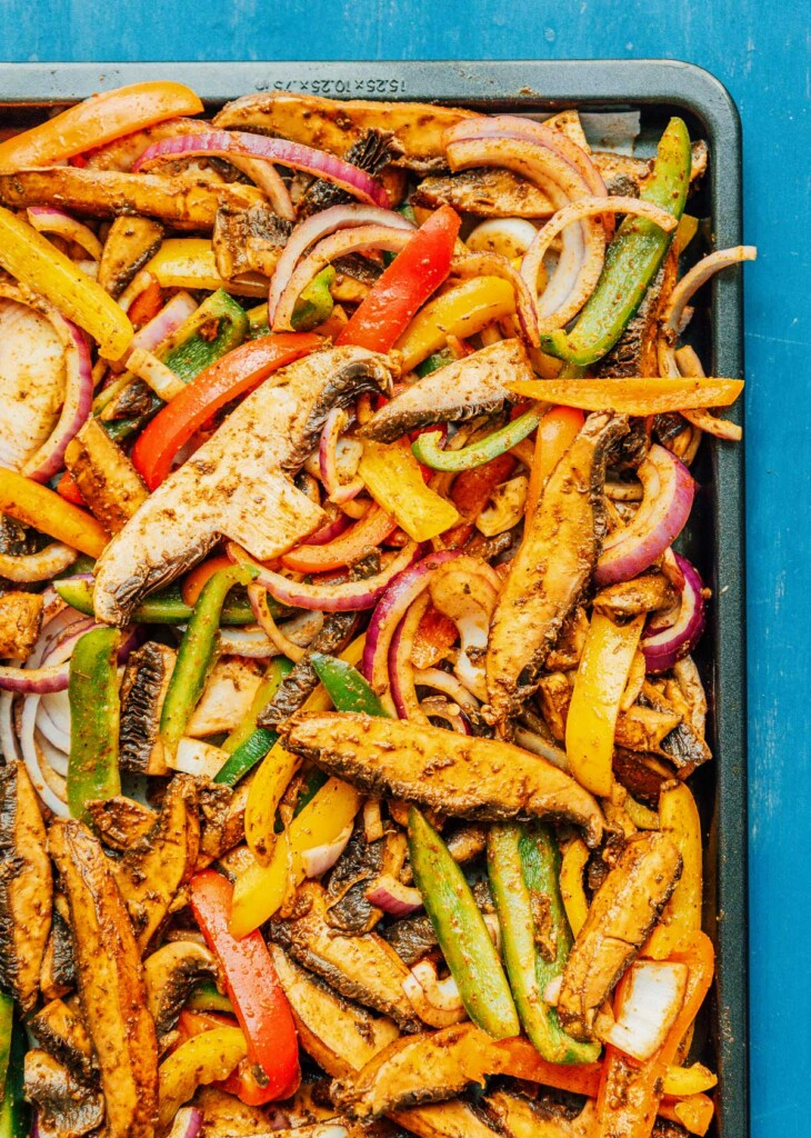A baking sheet topped with marinated mushrooms and veggies