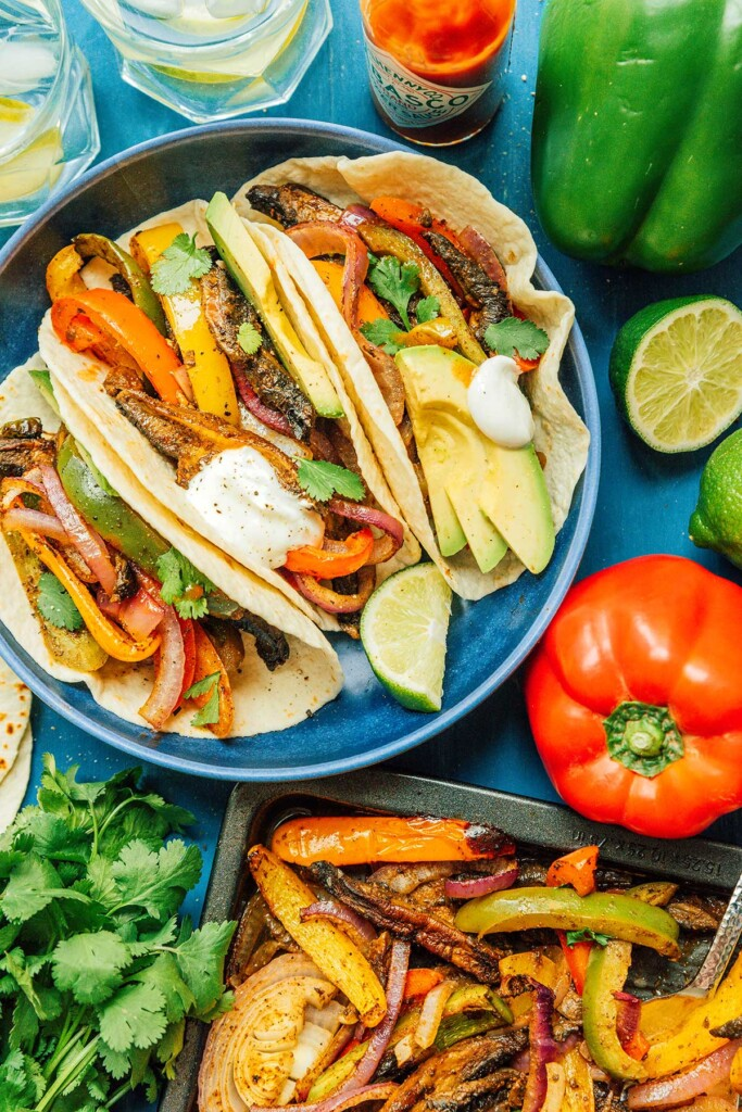 A blue plate filled with 3 vegetable fajitas and surrounded by various fajita ingredients