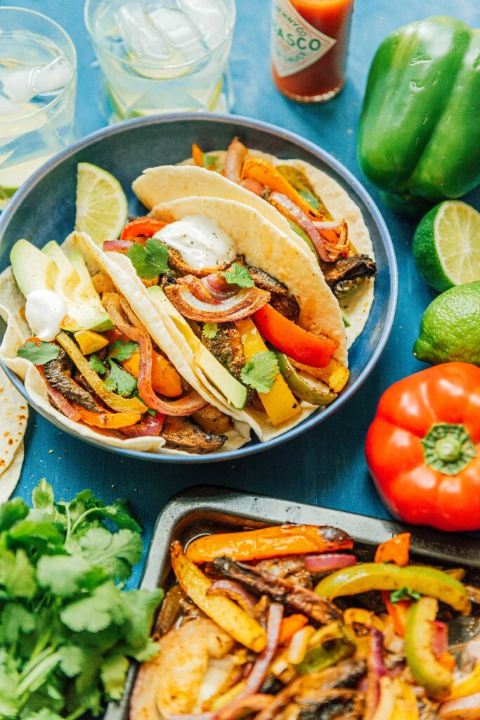 A blue plate filled with 3 veggie fajitas and surrounded by various fajita ingredients