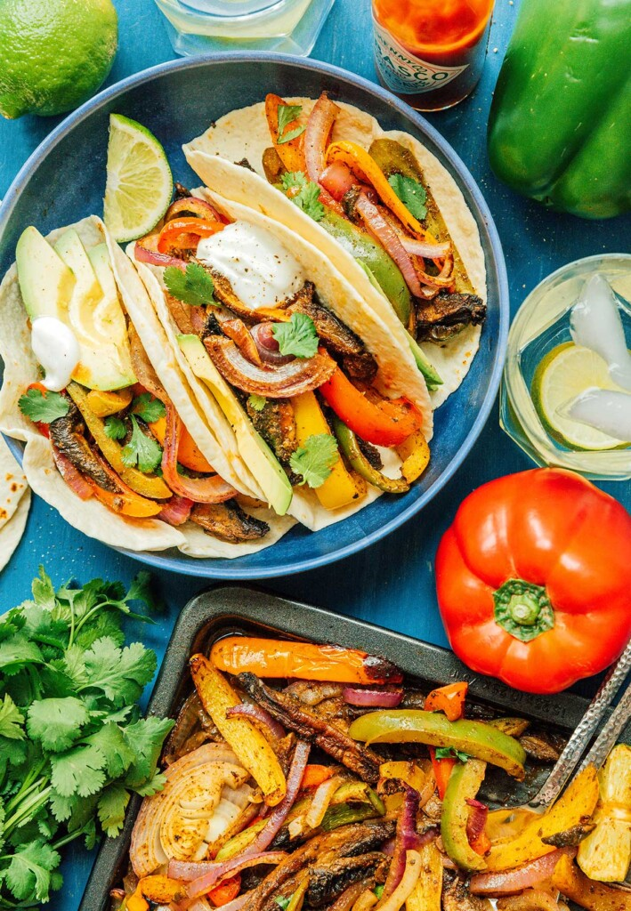 A blue plate filled with 3 vegan fajitas and surrounded by various fajita ingredients