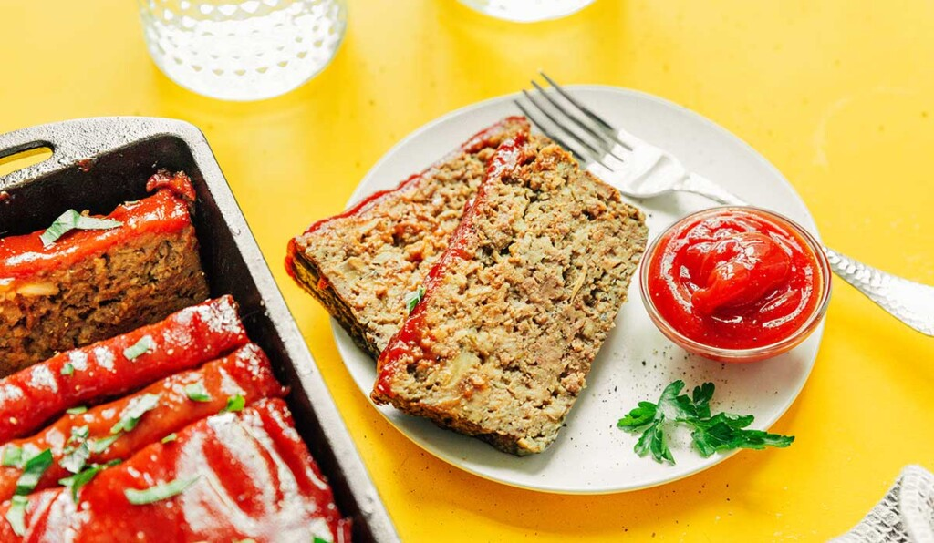 Two slices of mushroom meatloaf on a white plate along with a metal fork and dipping bowl of ketchup