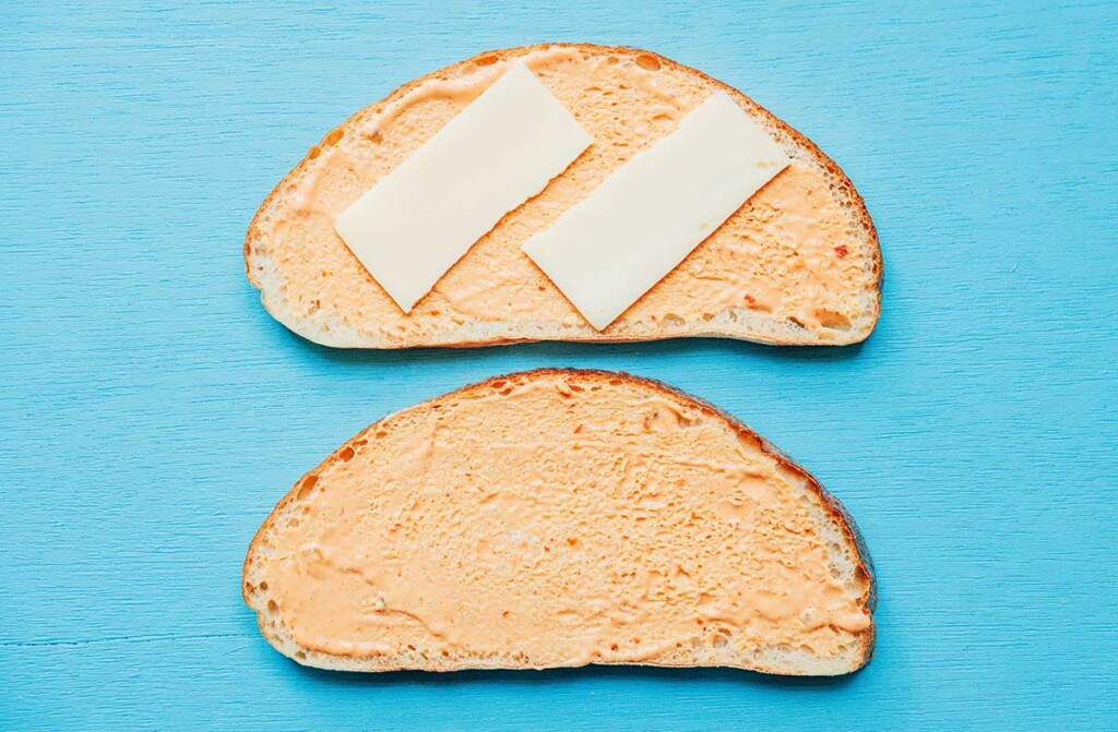 Two slices of bread coated in thousand island dressing, one of which has two small Swiss cheese slices on top