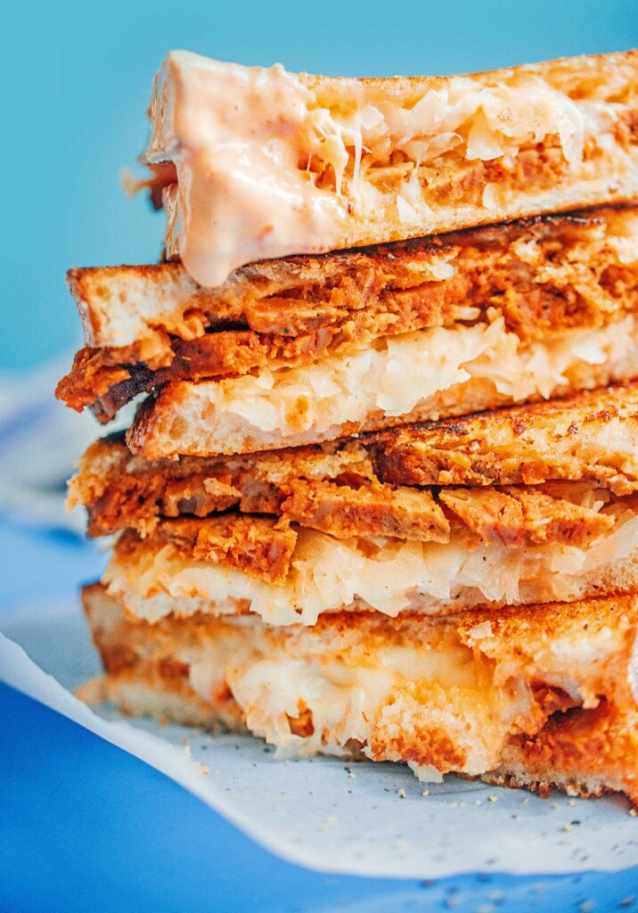 A close-up view of four halves of a seitan reuben sandwich stacked on top of one another