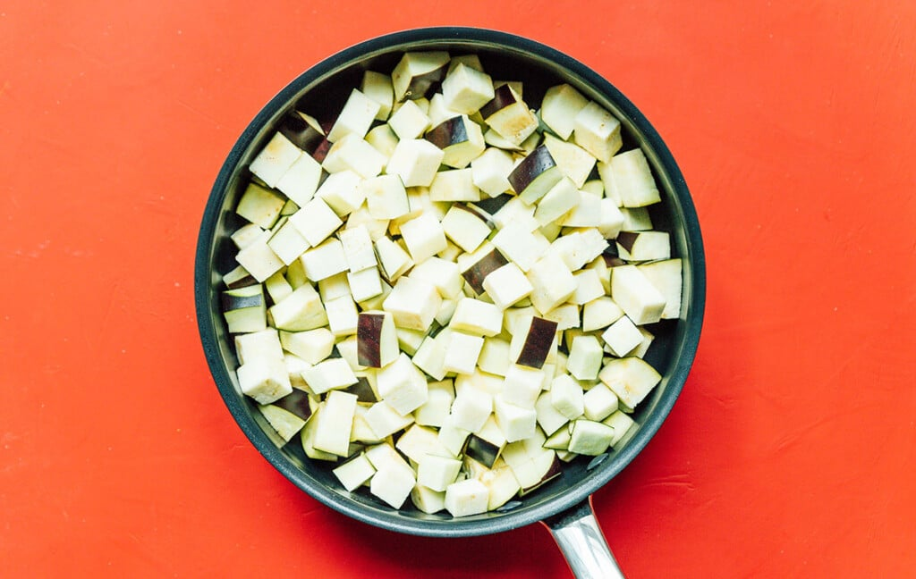 A skillet filled with uncooked, diced eggplant
