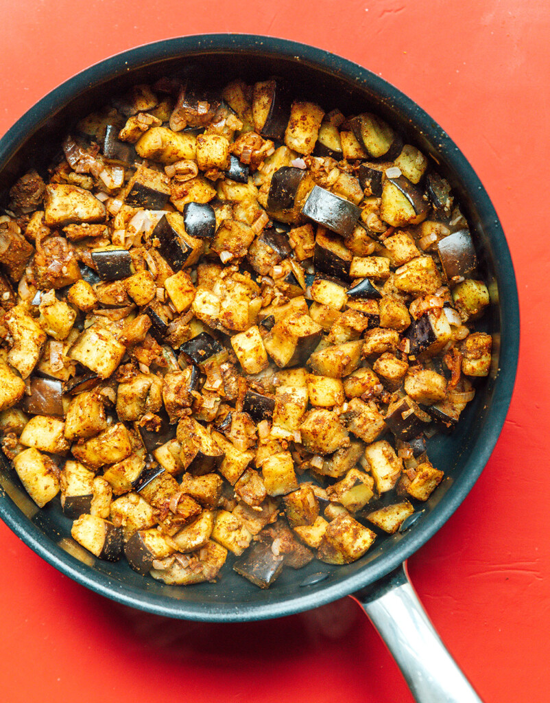 A skillet filled with diced eggplant, shallots, and garlic