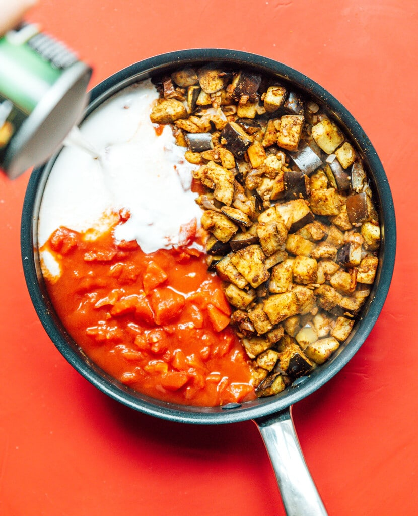 A skillet filled with diced eggplant, shallots, and garlic, along with a can of coconut milk and a can of diced tomatoes