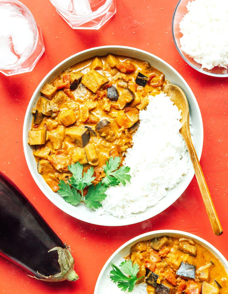 A white bowl filled with eggplant curry, white rice, and cilantro