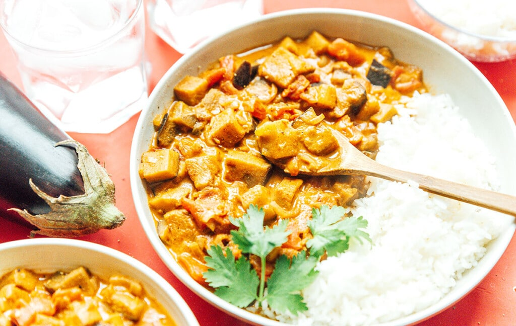 A wooden spoon dipped into a white bowl filled with eggplant curry, white rice, and cilantro