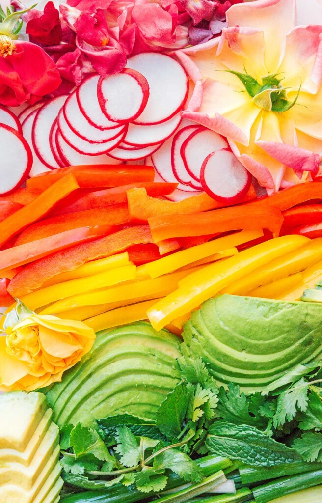 A close-up image detailing the veggies included in edible flower spring rolls, arranged by color