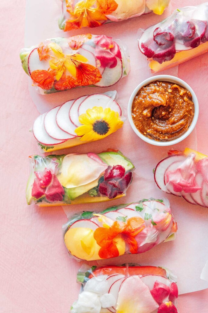 Eight edible flower spring rolls arranged on a pink background next to a dipping bowl of almond butter sauce