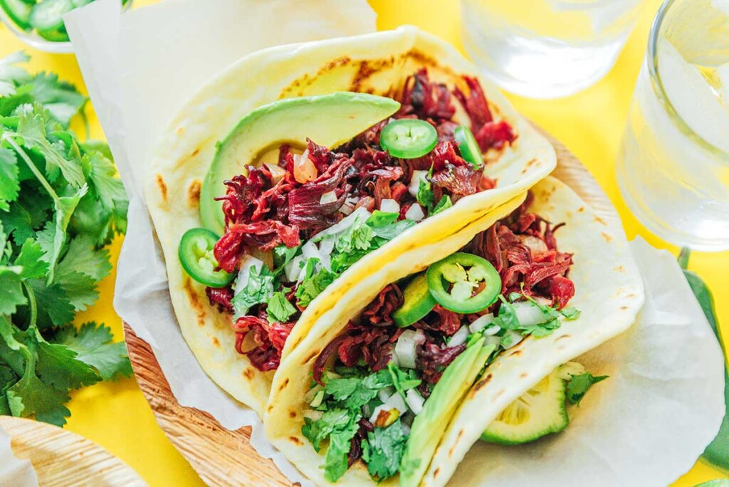 Two hibiscus tacos assembled on a wooden plate