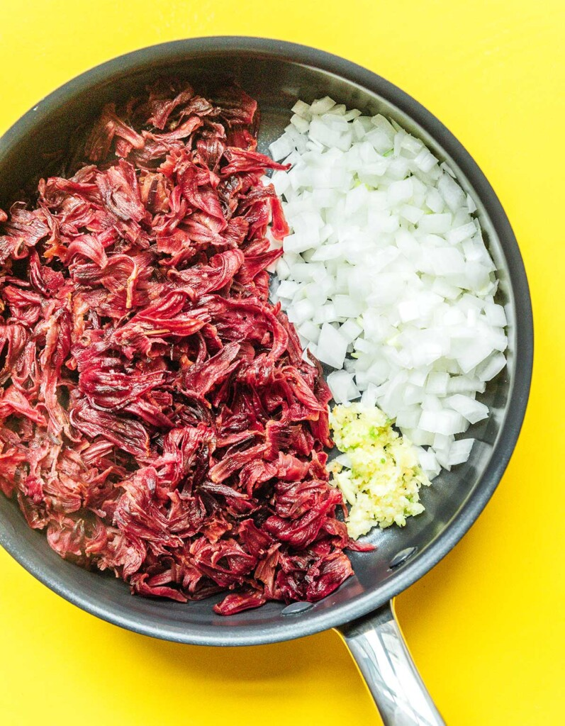 A skillet filled with boiled hibiscus pieces, chopped white onion, and minced garlic
