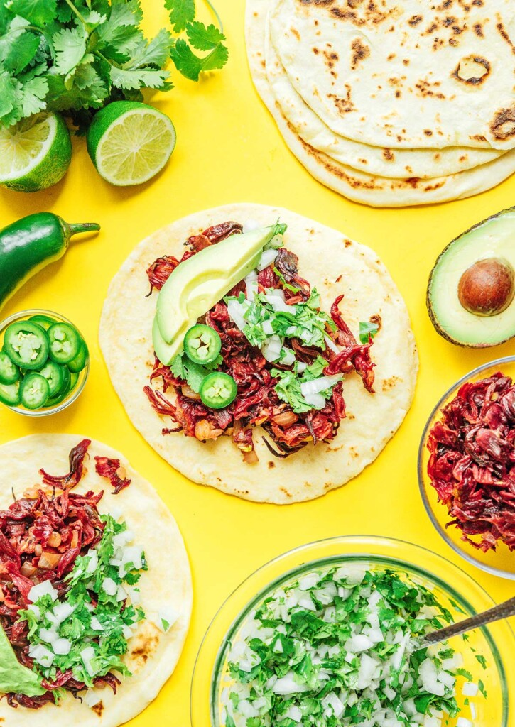 A taco shell filled with hibiscus taco fillings and surrounded by more tacos, half an avocado, jalapeño slices, and other ingredients