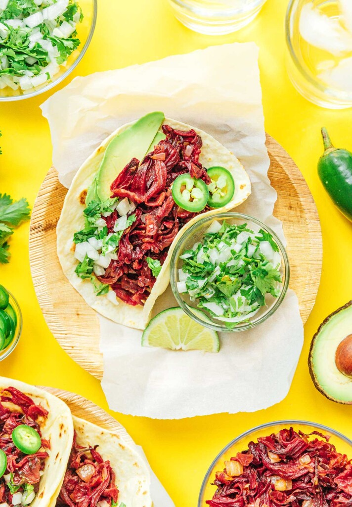 A hibiscus taco on a wooden plate alongside a bowl of onion and cilantro relish and one lime slice