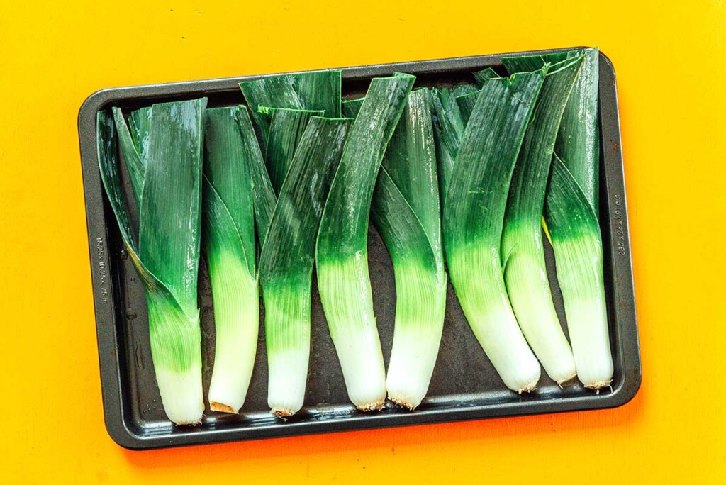 A baking sheet filled with a row of eight leek halves laying cutside down