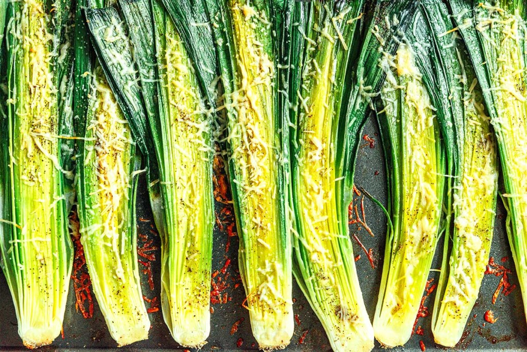 Eight leek halves coated in parmesan cheese sitting cutside up on a baking tray