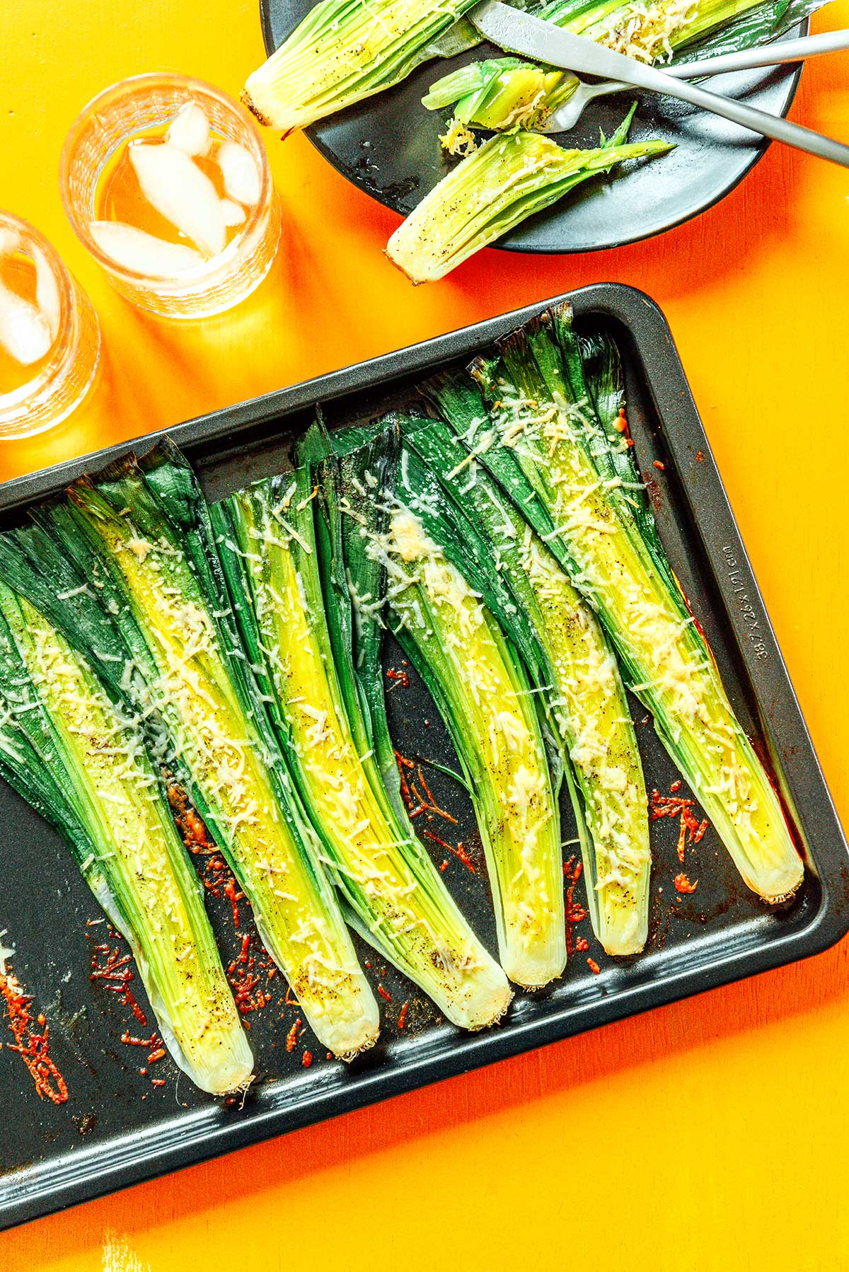 A tray of six leek halves fresh out of the oven with parmesan coated on top