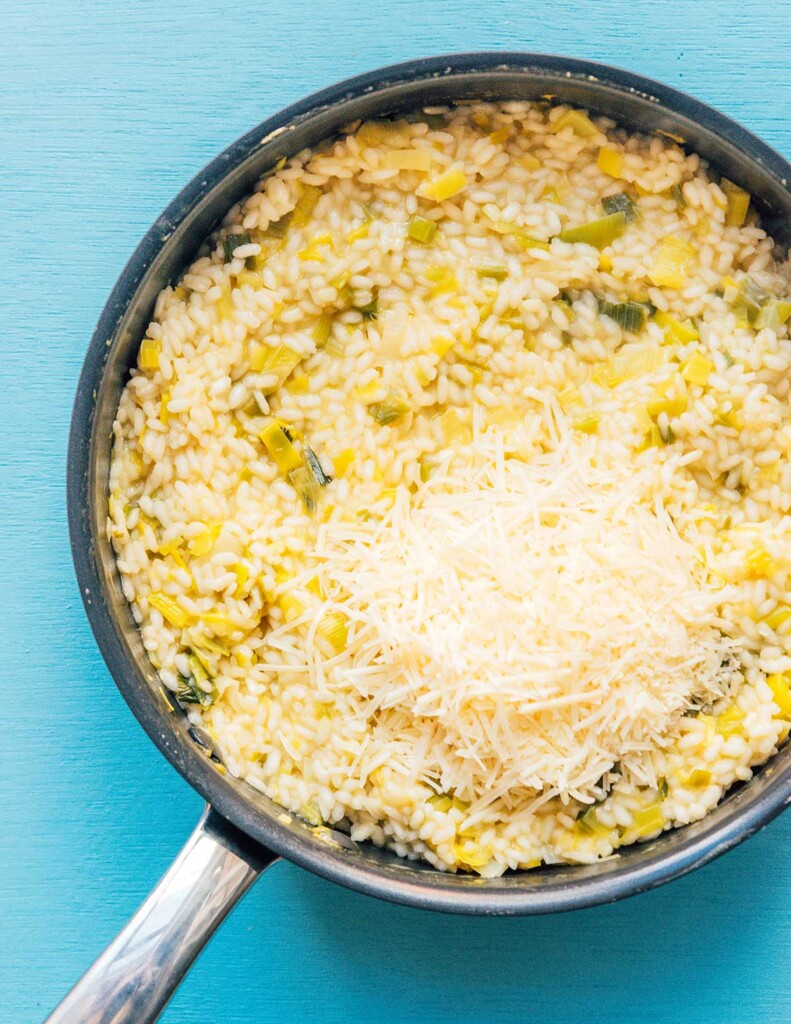 A skillet filled with leek risotto and shredded parmesan cheese