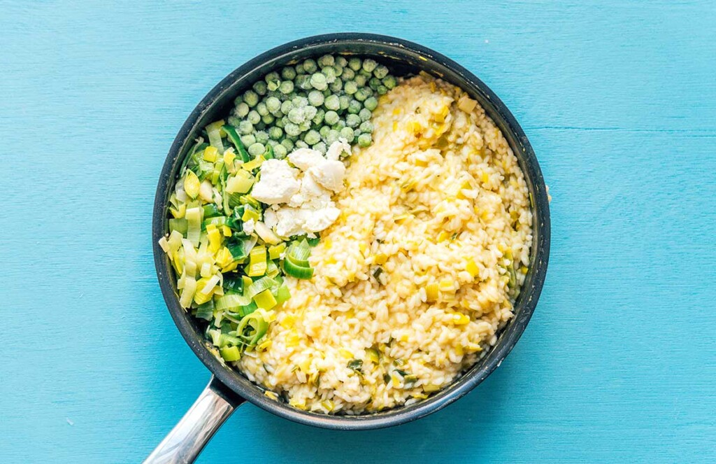 A skillet filled with arborio rice, leeks, frozen peas, and goat cheese