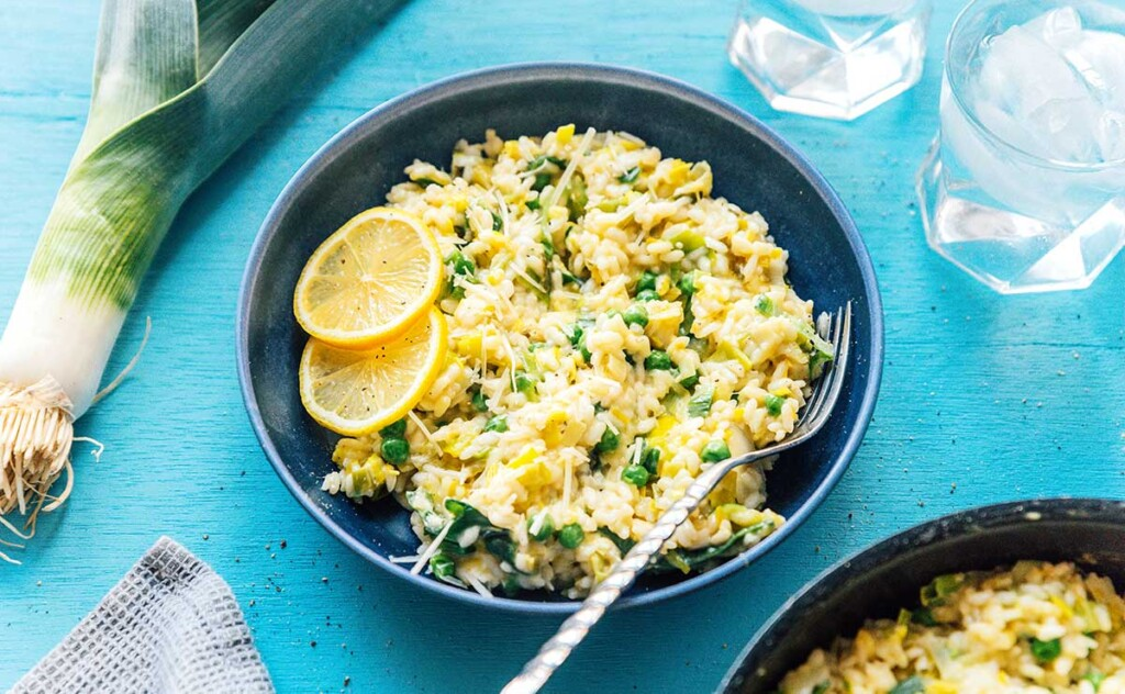 A blue bowl filled with leek risotto and topped with lemon slices