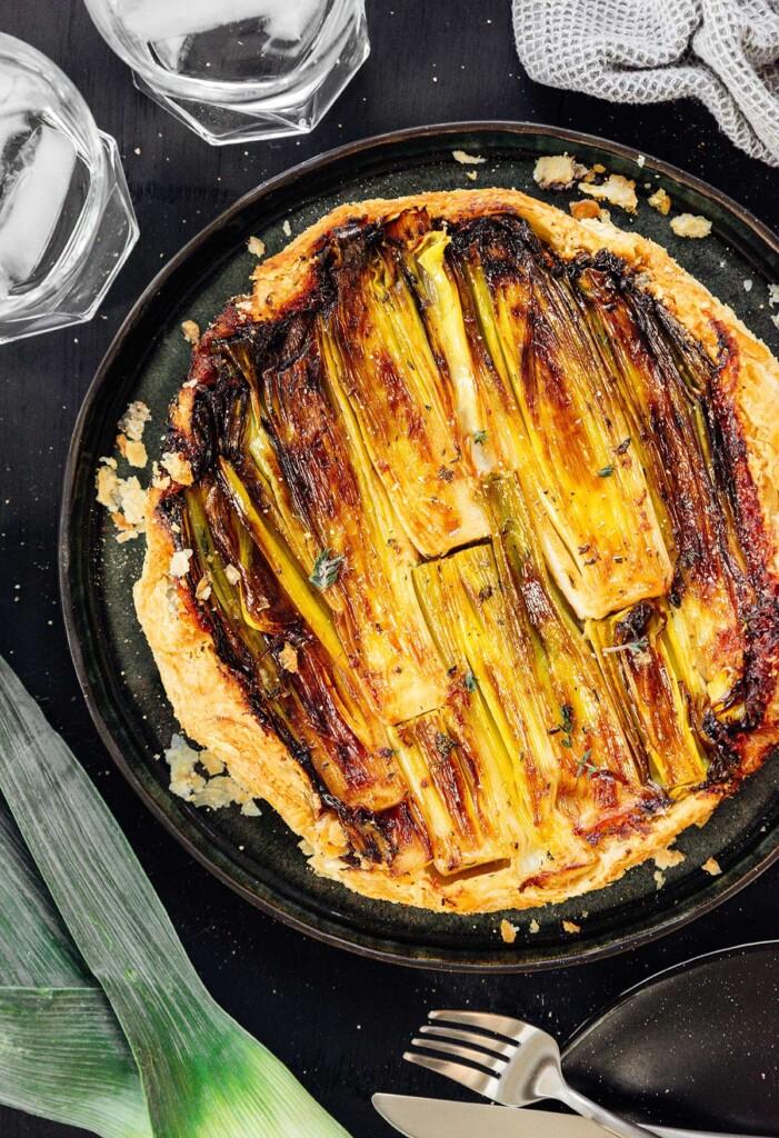 A freshly cooked upside down leek tart in a black plate