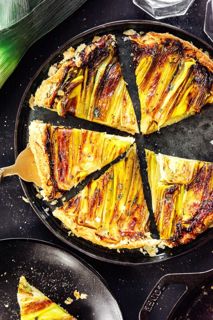A gold spatula scooping a slice of leek tart from a skillet containing 5 pieces