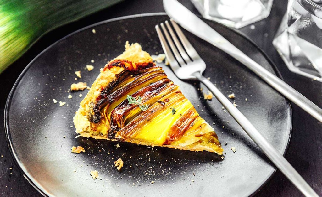 One slice of upside down leek tart on a black plate with a fork and knife