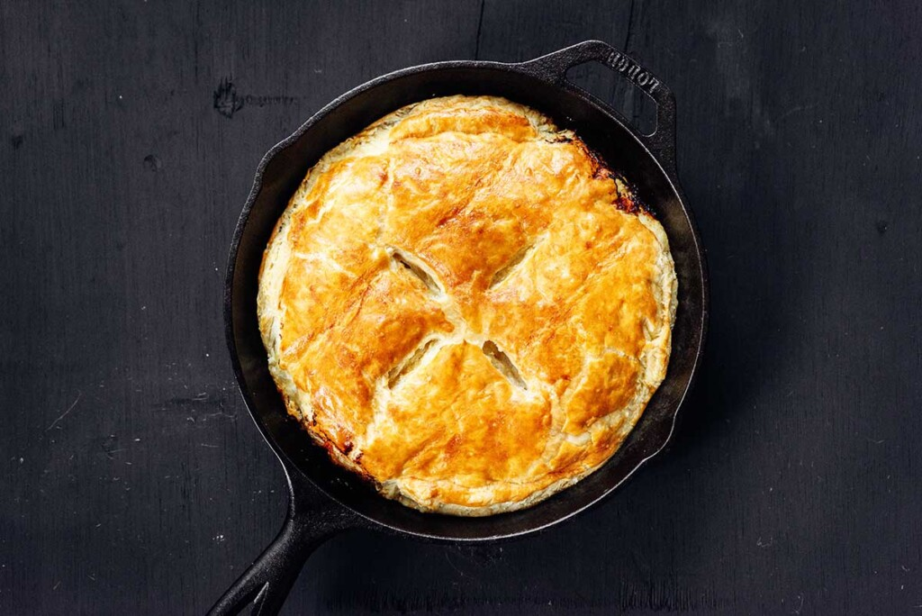A skillet filled with a puff pastry topped leek tart