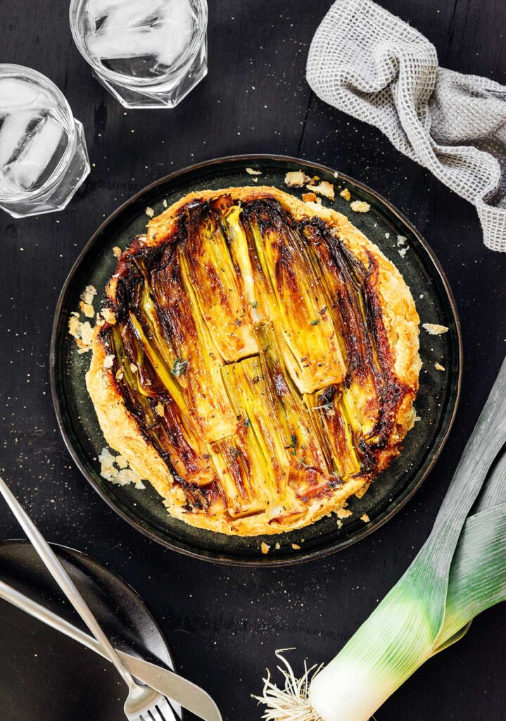 A bird's eye view of a large black plate filled with a freshly cooked, whole upside down leek tart
