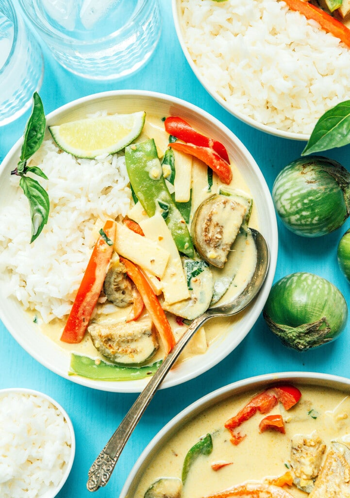 A white bowl filled with Thai green curry on top of a bed of rice and garnished with basil and a lime wedge