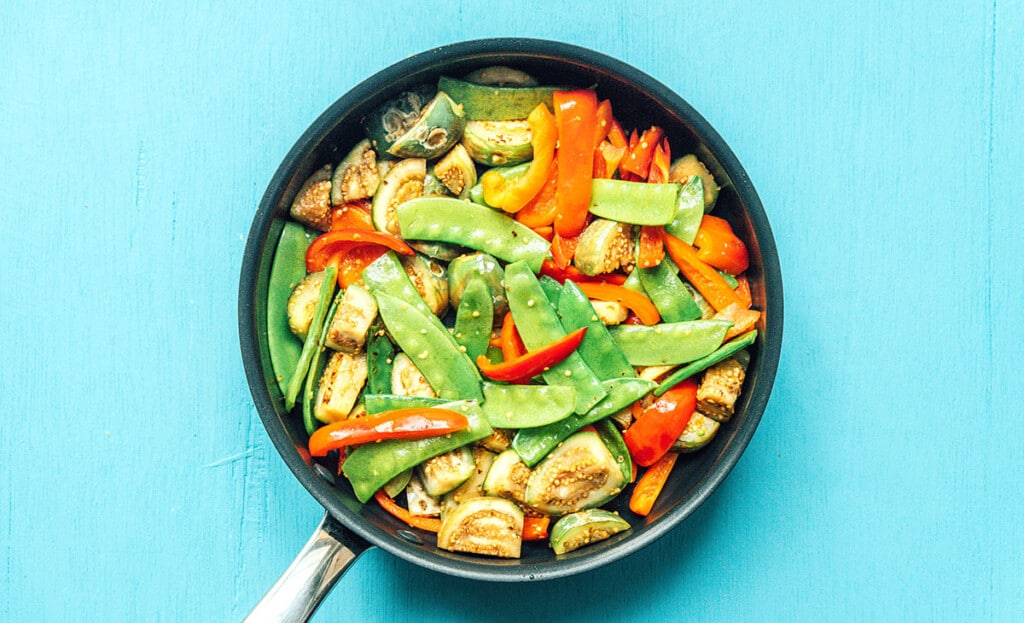 A pan filled with eggplant, snow peas, and red bell pepper