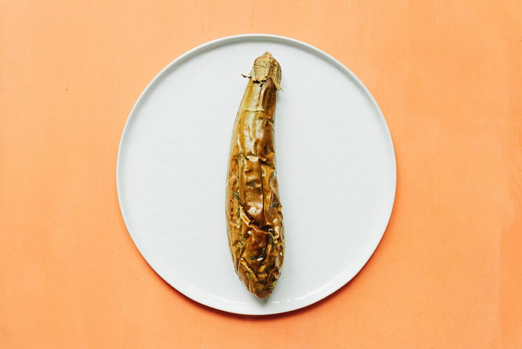 A broiled Filipino eggplant on a white plate