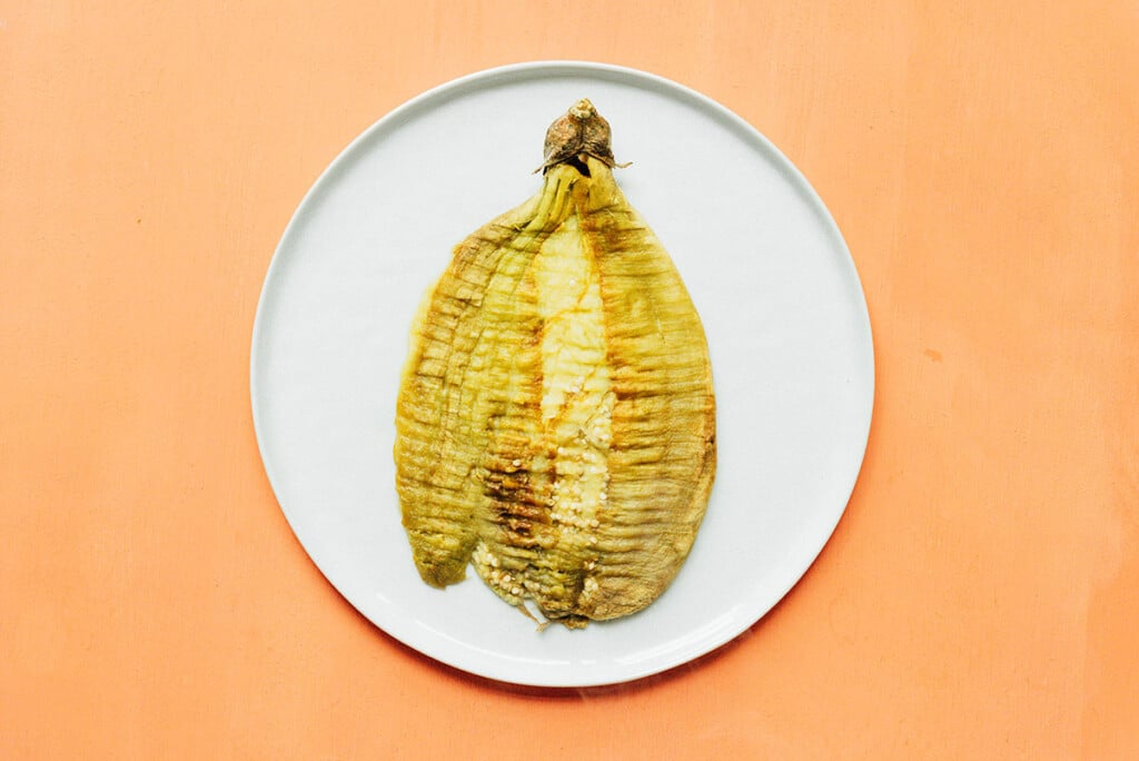 A squished Filipino eggplant on a white plate