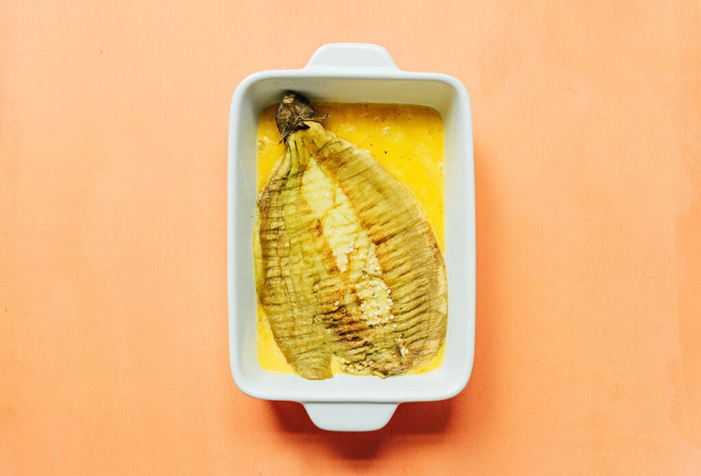 A squished Filipino eggplant in a casserole dish filled with egg wash
