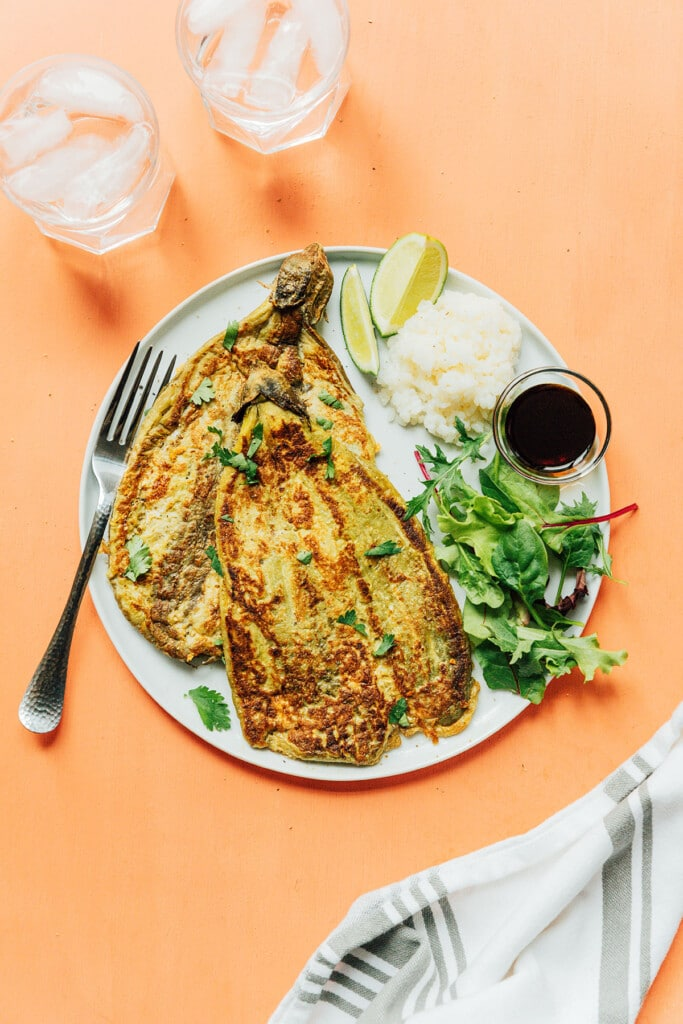A white plate filled with two tortang taglons, greens, rice, and soy sauce