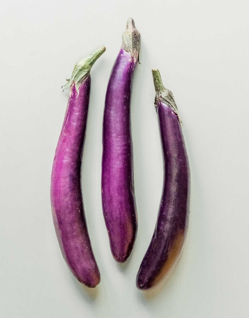 Three Chinese eggplants arranged in a row on a gray background